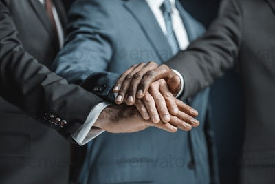 cropped shot of multiethnic group of businessmen holding hands together