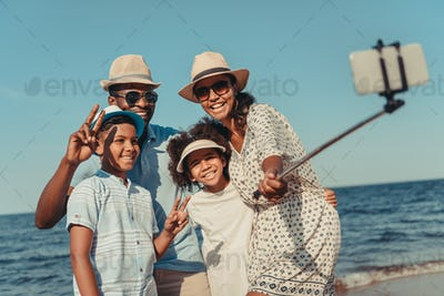 happy african american family taking selfie with smartphone on beach