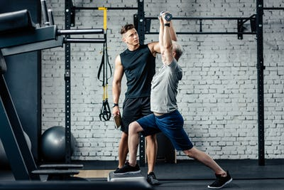senior sportsman doing lunges with dumbbells in gym with trainer near