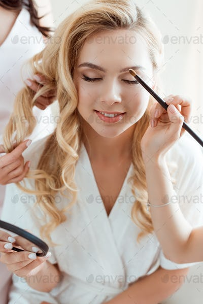 young woman getting makeup before wedding ceremony