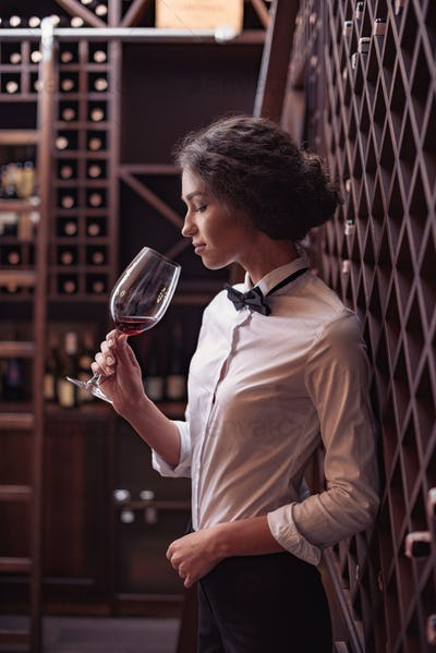 Young beautiful woman sommelier tasting red wine in wine cellar
