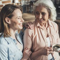 adult daughter talking with senior mother in kitchen