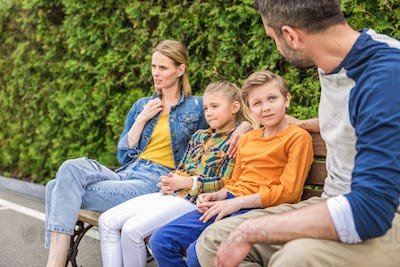 caucasian family talking while sitting together on bench at park