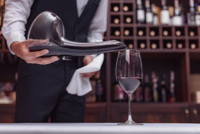 Cropped view sommelier pouring red wine from decanter into glass at table in cellar