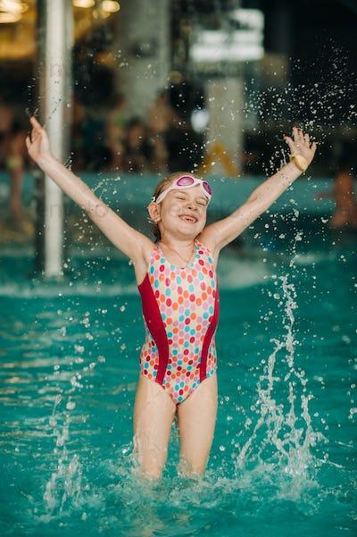 Small happy girl enjoys hot summer day at swimming pool
