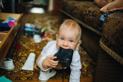 Infant Baby Child Boy Six Months Old is Takes his Shoe in the Mouth