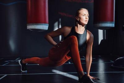 Serious female boxer warming up in dark sport club
