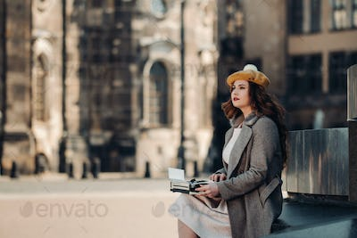 a stylish young beautiful girl is sitting and typing in the Old town of Dresden.Germany