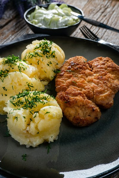 Pork chop served with mashed potatoes and cucumber salad.