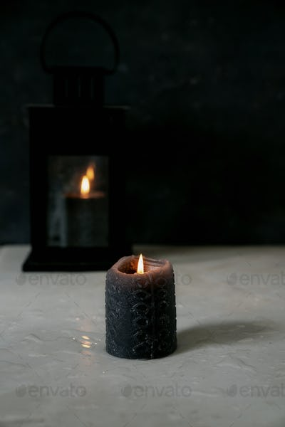 Partly burned black candle and vintage lantern with burning candle