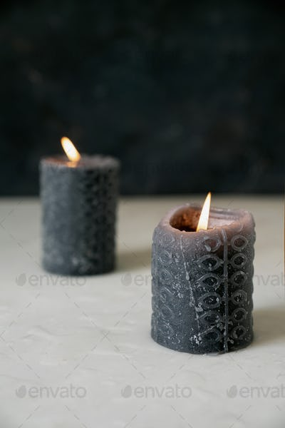 Two burning black candles on a marble background