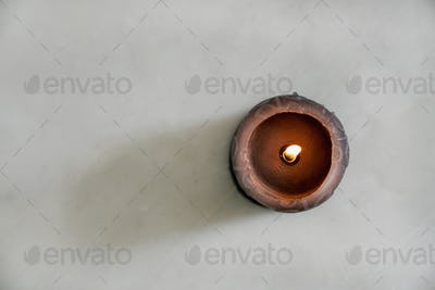 Burning black candle on a marble background