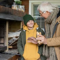 Grandfather in warm casualwear explaining his grandson how to burn fireplace