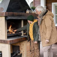 Cute boy in warm jacket and beanie standing by fireplace while putting firewoods