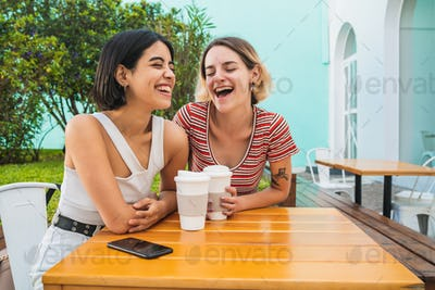 Loving lesbian couple having a date at coffee shop.