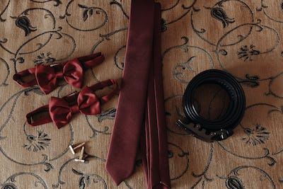 stylish red bow-tie and tie with belt and cufflinks on bed