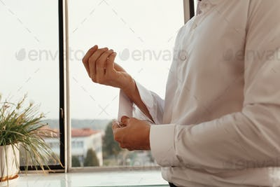 stylish groom getting ready in morning, putting on white shirt golden cufflinks