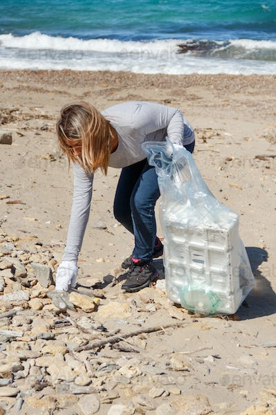 Young woman cleaning beach area from plastic