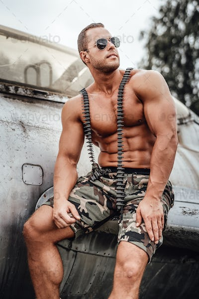 Military bodybuilder sitting on airplane's wing