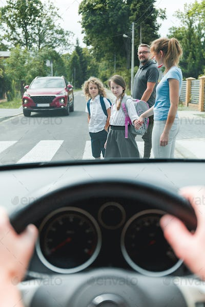 Drivers point of view of family with children crossing a street on pedestrian area