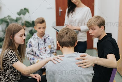 Group of teenagers sitting in a circle and comforts a colleague during a class with a psychologist
