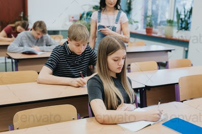 Young girl sitting at the table during economy class at school