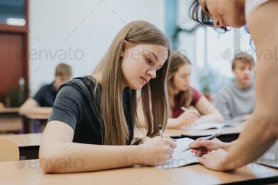 Teenage girl sitting at the table during math class at school