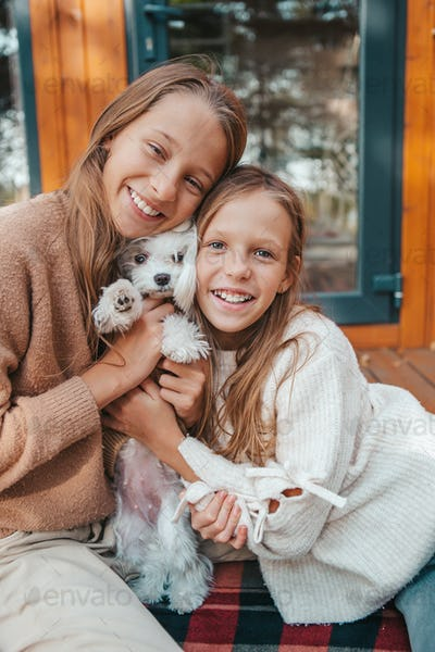 Happy kids sitting on the terrace of their house in autumn