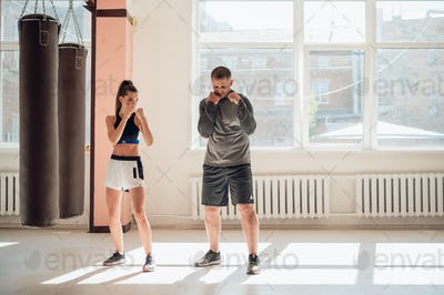 A young attractive boxing coach prepares a pretty girl for competition