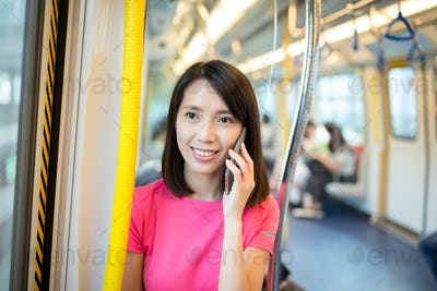 Woman talk to cellphone at train compartment