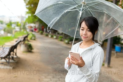 Woman holding an umbrella and using mobile phone at outdoor