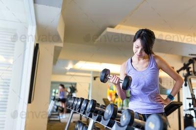 Fitness girl lifting dumbbell