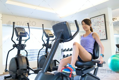 Woman exercising legs doing cardio training on bicycle