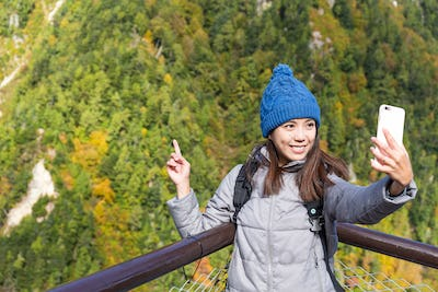 Woman taking selfie by mobile phone in Mount Tate
