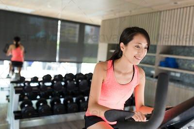Woman training on bike in gym
