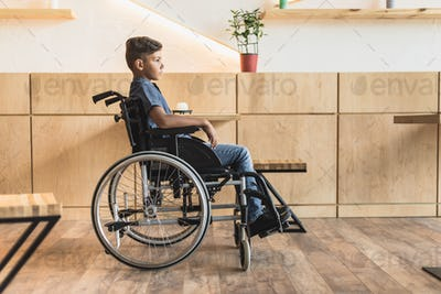 side view of little african-american boy in wheelchair