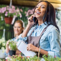 smiling young african american florist holding notebook and talking on smartphone while colleague