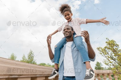 low angle view of smiling african american father and daughter piggybacking together in park