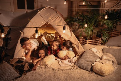 multiethnic group of children resting in handmade tent together at home