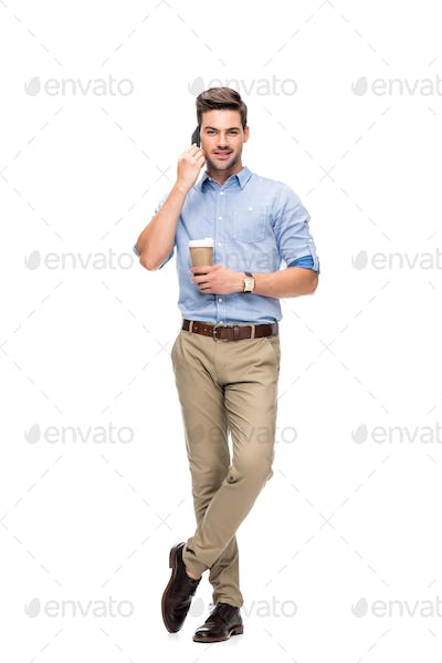 handsome man talking by phone with coffee to go in hand isolated on white