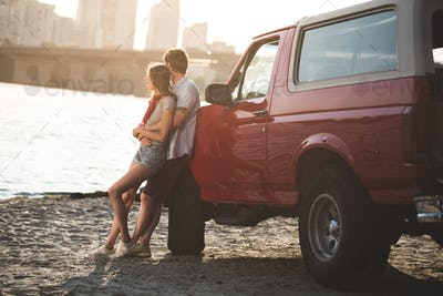 couple embracing on beach and leaning back on classical car