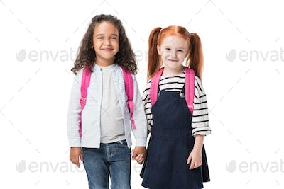 adorable multiethnic schoolgirls with backpacks holding hands and smiling at camera isolated on