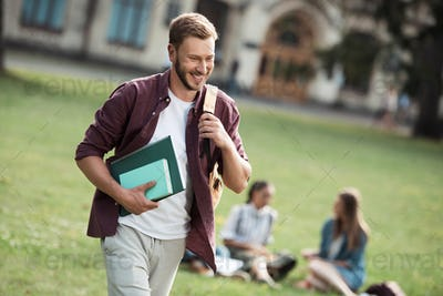 handsome smiling male student with backpack and books walking near university