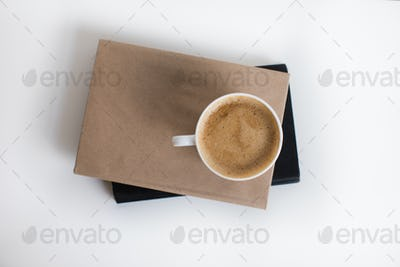 top view of white cup of coffee on two books, isolated on white