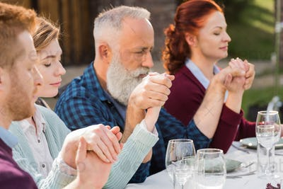 family holding hands while praying during dinner at countryside