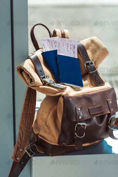 close up view of backpack, passports and tickets on airport windowsill