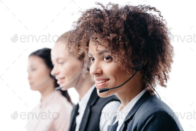 multiethnic female operators working with headset, isolated on white