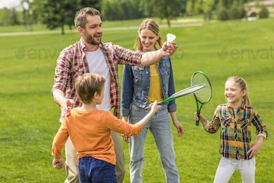 happy casual family playing badminton in park at daytime