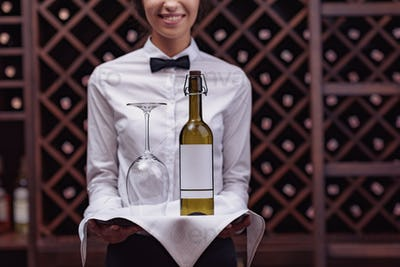 Cropped view woman sommelier standing with bottle of wine and glass on tray in cellar