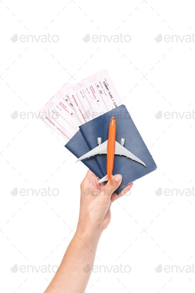 cropped shot of human hand holding passports with tickets and small model of plane isolated on white